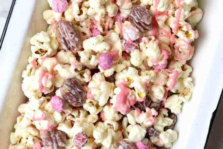 A pan of popcorn with nuts and candy covered chocolates.