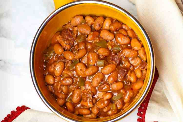 Saucy Pork And Beans in a crock with a serving spoon.