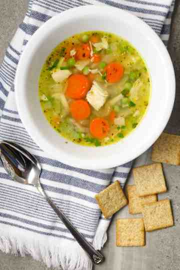 A bowl of soup with a spoon and crackers.