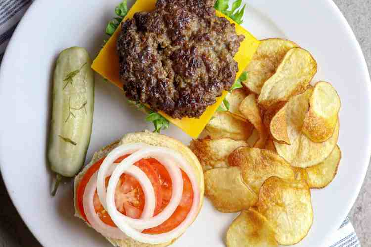 A white plate with an open faced Best Sizzle Burger Recipe and fries.