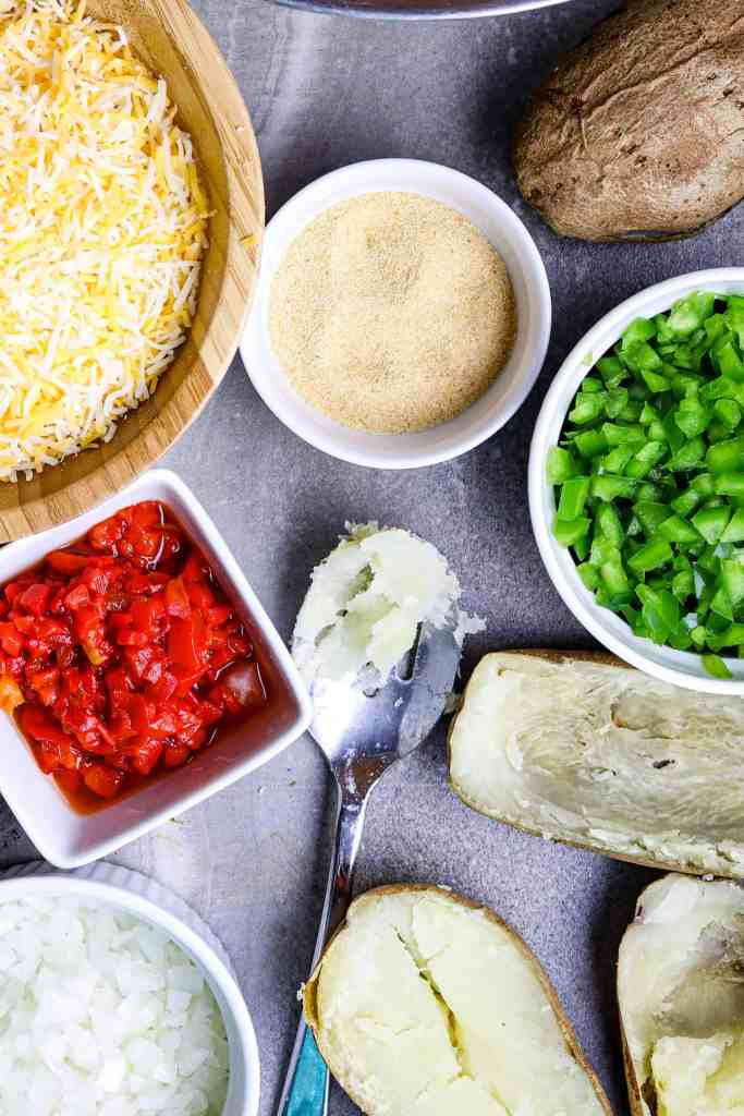 Ingredients of grated cheese, pimento, garlic granules, and green pepper on a gray stone counter.