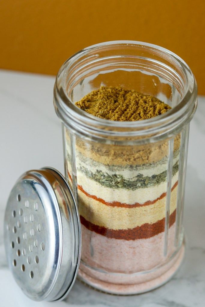 A glass container with layered with different spices.