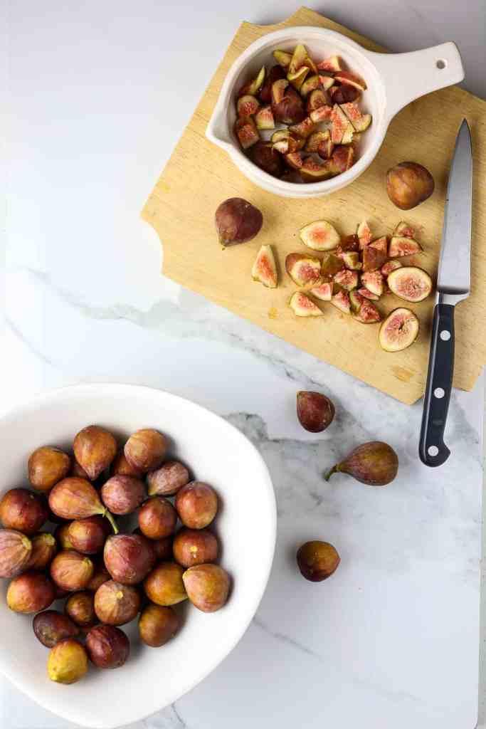 A cutting board with cut up fresh figs.