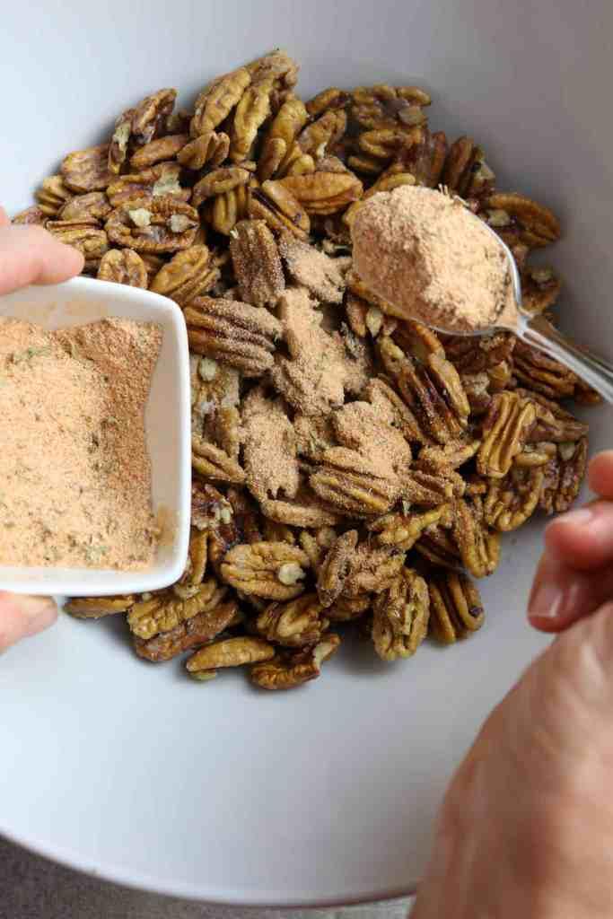 Sprinkling a spoonful of Cajun seasoning onto nuts.