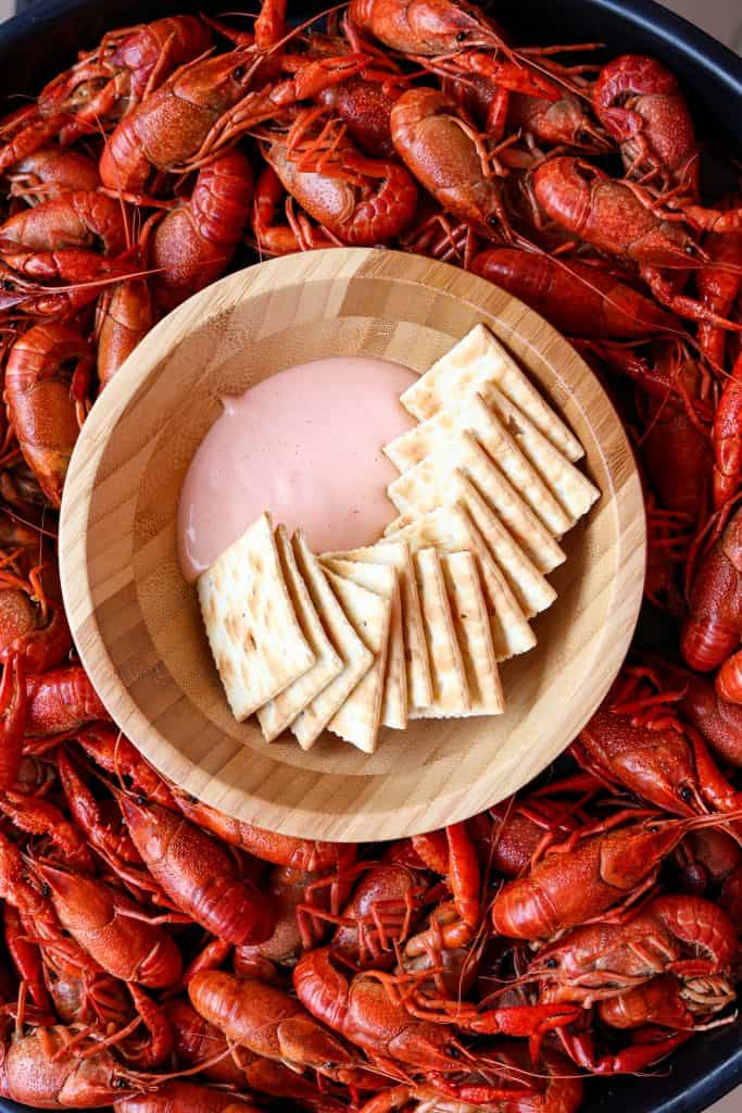 Bowl with dip and crackers in a pan of crawfish.