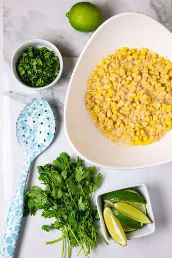 A bowl of corn with a bowl of limes and sprigs of cilantro and a serving spoon.