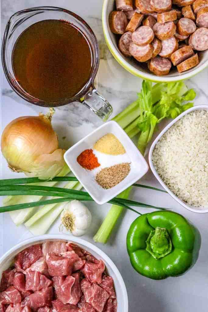 Ingredients of the Cajun trinity, spices, pork meat, sausage, broth, and seasonings.