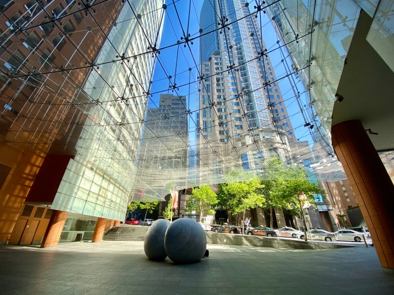 Looking up through a large glass awning with boulder-like sculptures in the foreground