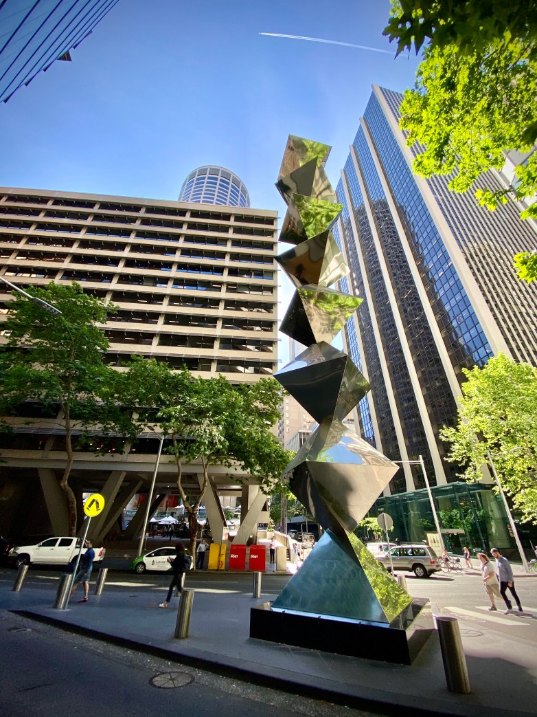 Looking up at the sky with an angular, reflective sculpture in the foreground and buildings in the background