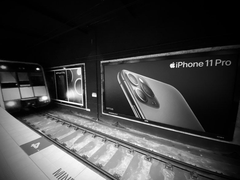 A train arrives on the tracks from the left, moving past large iPhone 11 Pro billboards to the right.
