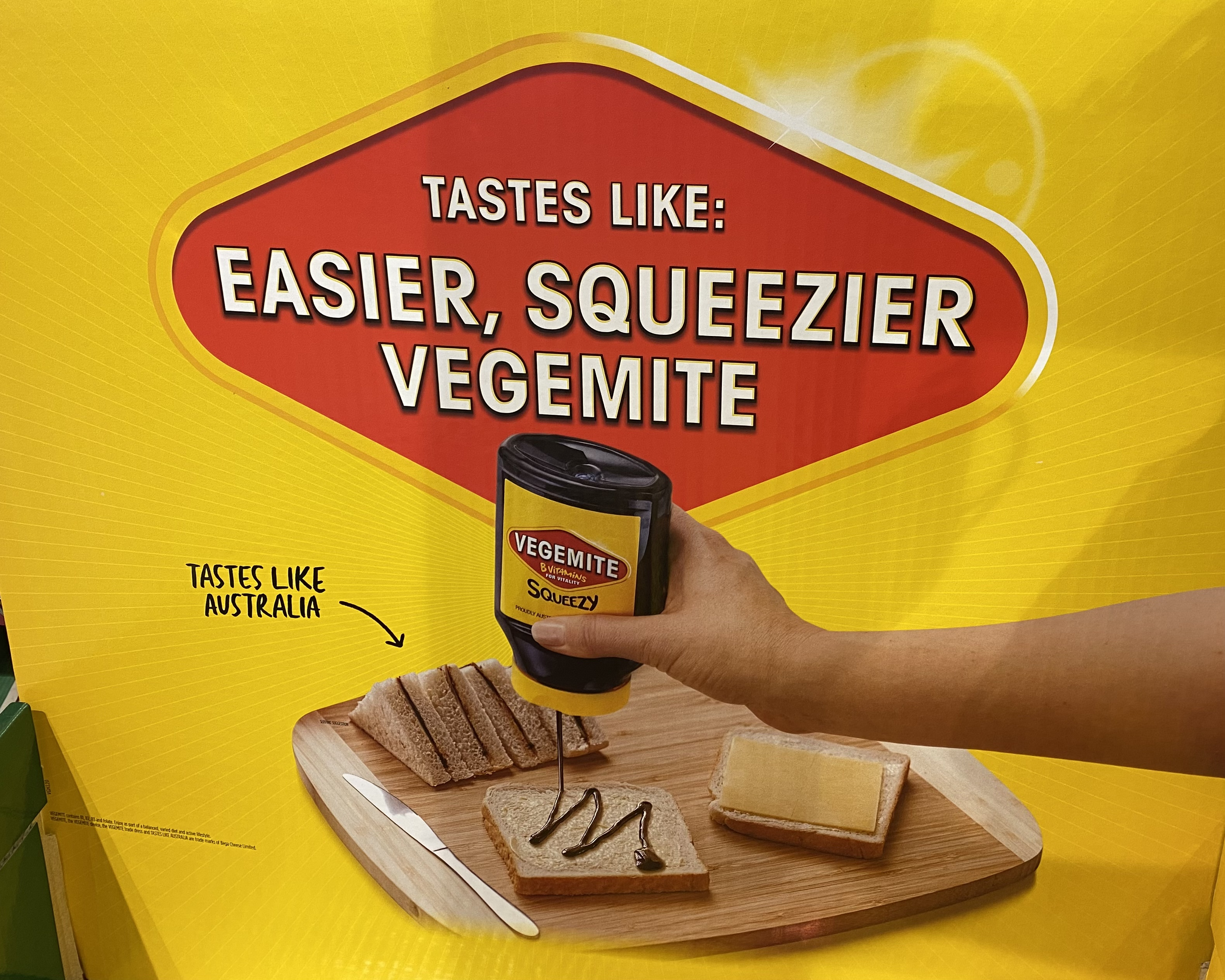 An ad that shows a hand squeezing Vegemite out of a bottle onto bread, with the caption: 'Tastes like: easier, squeezier Vegemite (tastes like Australia)'