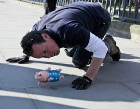 Performance Artist Mark McGowan noses his pig down the road
