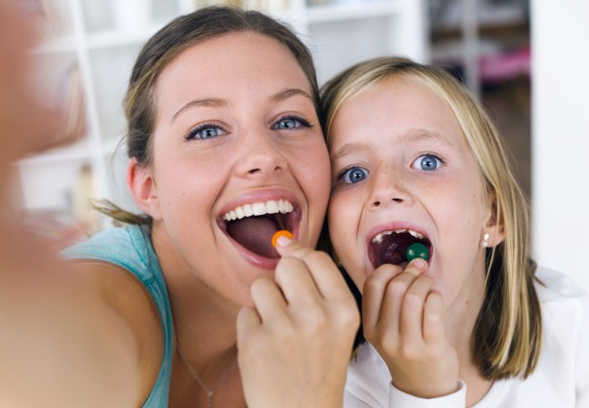 Portrait of young mother and daughter taking a selfie while eating sweets.