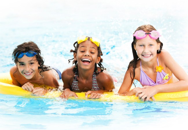 Smiling children wearing snorkel goggles and floating on a yellow raft