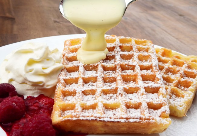 Gingerbread waffles on plate with whipped cream and raspberries