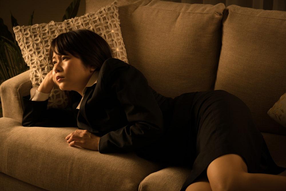 ソファーでうたた寝をするビジネスウーマン、疲労