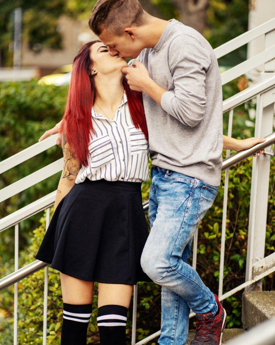 sexy Schulmädchen küsst Kerl auf den Stufen