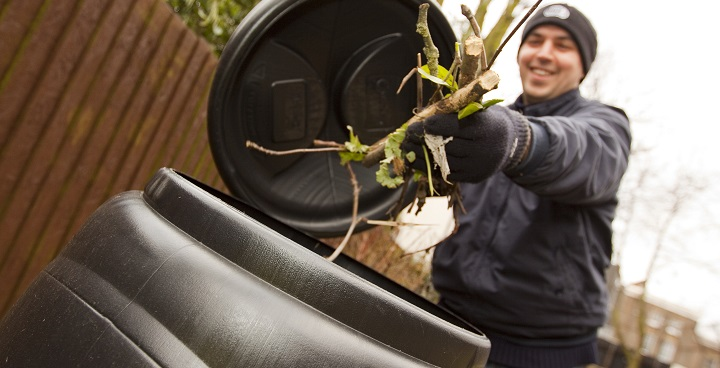 Man in wooly hat holding compost bin lid open with one hand while putting cut tree branch in with the other
