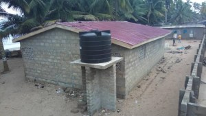 Backside of public washroom with water tank in Lower Saltpond, Ghana