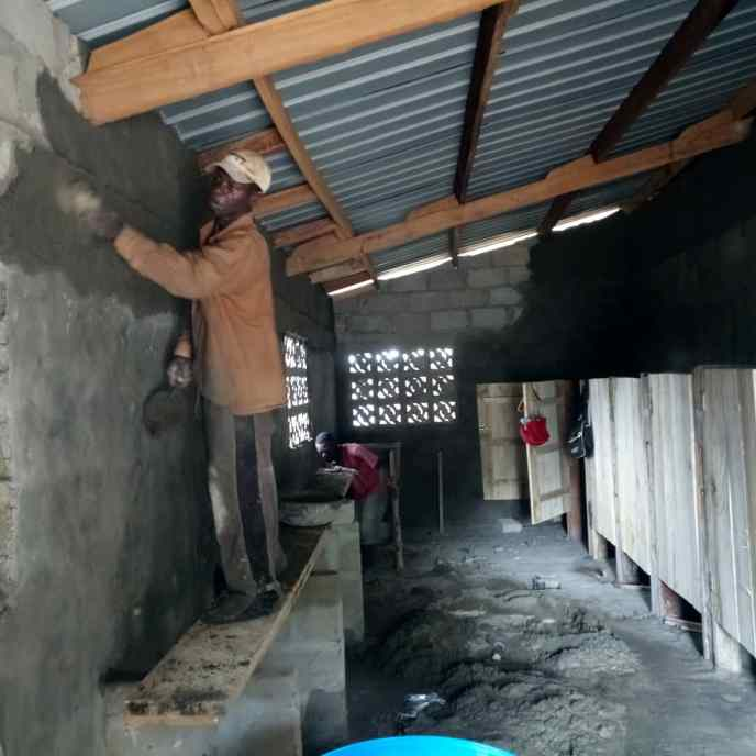 Parging of public washroom walls inside building