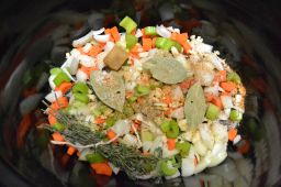 Add veggies, herbs, & seasoning to the slow cooker.