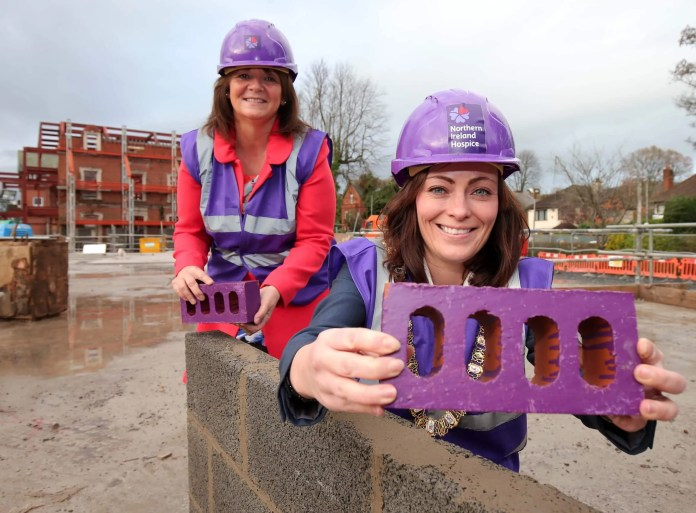 Priscilla Roche, whose son was cared for by NI Hospice last year, joins Lord Mayor of Belfast Nichola Mallon at the Somerton Road construction site as the charity reaches a major milestone in its journey to rebuild the adult Hospice in North Belfast.