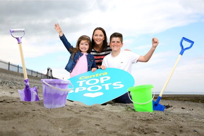 CAPTION: Centra's Jennifer Morton along with Tiernan Smyth (11) and Anya Smyth (5) from Newcastle, have fun on the beach as they help launch the search for Centra's Top Beach Spot, supported by Tourism NI. For a chance to win fantastic prizes, nominate your favourite beach spot atwww.centra.co.uk/topspots