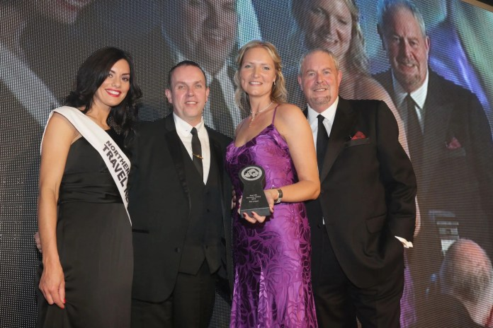 Andrea Hunter, Business Development Manager of Aer Lingus NI receives the Award for the 'Best UK Domestic Airline' from Andrew Bolton, of category sponsors Celebrity Cruises at the 24th Northern Ireland Travel and Tourism Awards. Looking on are compere Gerry Kelly and NI Travel News promotions girl Zara Shaw.