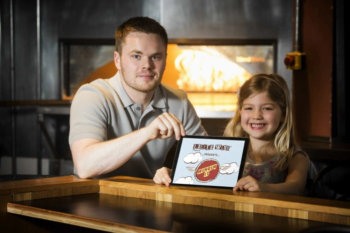 APPY DAYS FOR LITTLE WING 2: Pictured: Ariana Loughlin, age 5 gets to grips with 'Wingin It' alongside Little Wing Director Luke Wolsey. Northern Ireland's favourite pizzeria, Little Wing has launched an exciting new mobile game. The popular home grown pizzeria group partnered with University of Ulster design students, tasking them with creating the design concept for their first ever mobile game, 'Wingin' It', which is now available to download free from the Apple App Store and Google Play. The game challenges players to make pizzas from the Little Wing menu; gamers must catch toppings on a winged pizza base as they fall from the sky whilst avoiding hitting any pesky clouds. This is the next stage in a series of ongoing investments in Little Wing's digital offering, following the launch of its new website www.littlewingpizzeria.com earlier this year. The new Little Wing 'Wingin' It' game is available now for free download on the Apple App Store and Google Play. For further information visit www.littlewingpizzeria.com, or follow Little Wing on Twitter, Facebook and Instagram (LittleWingPizzeria).