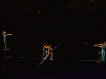 girl climbing on to another tightrope walker's back