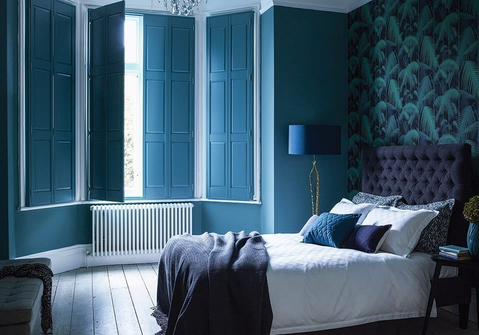 solid window shutters in a dark blue bedroom with grand wallpaper