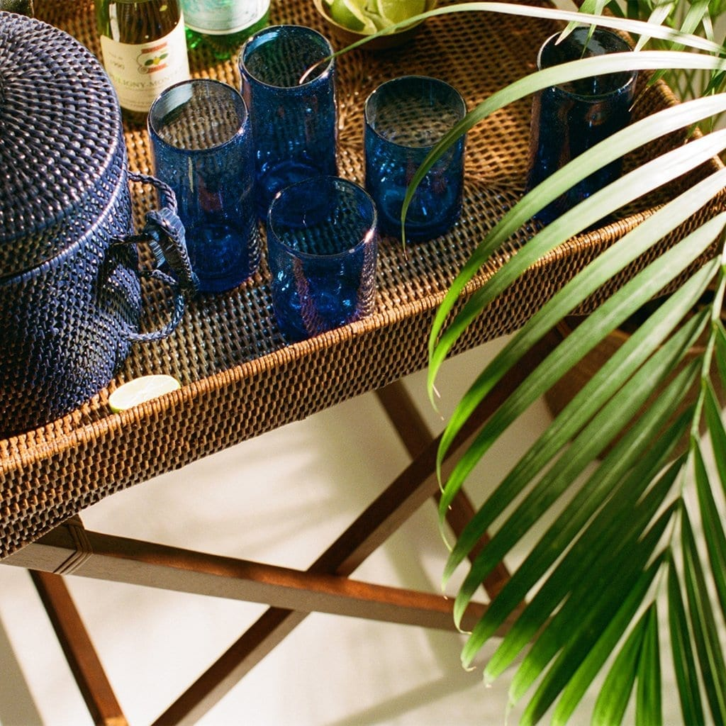 Blue glasses and wicker ice bucket on a tray
