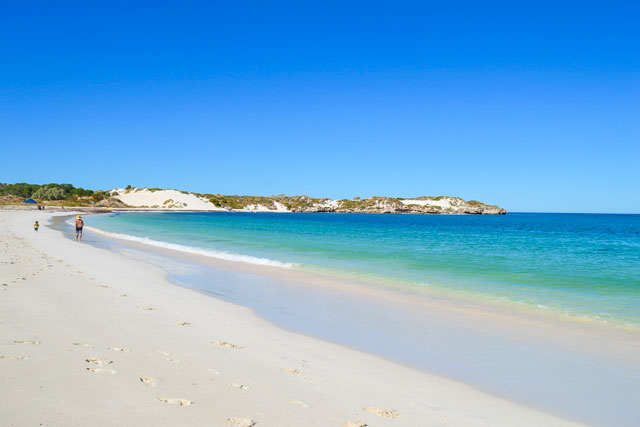 Walking on the white sand beside the turquoise water at Sandy Cape