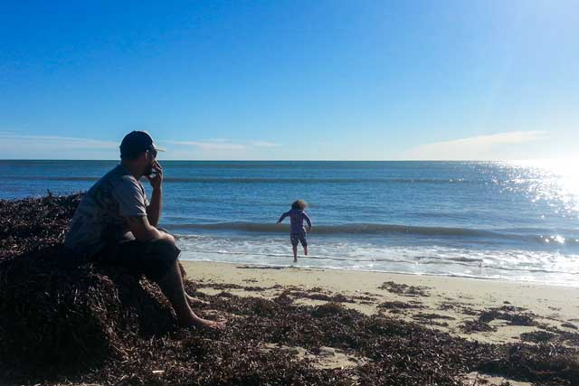 Em splashing in the water while Rick sits on a pile of seaweed