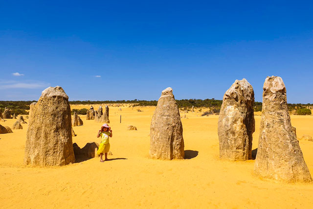 Em dressed in yellow in a yellow desert standing among the Pinnacles
