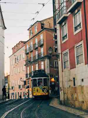 Lisbon cable car turning the corner in front of different shades of pink buildings in Alfama
