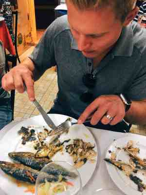 Man eating the sardine fish delicacy in Lisbon