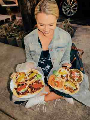 Girl holding two plates of vegan tacos