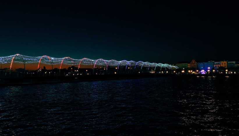Queen Emma Floating Bridge lit up with rainbow lights, one of the top things to do in Curacao