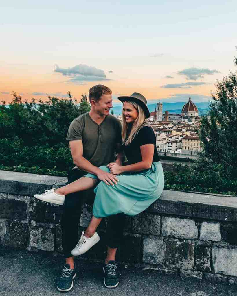 Couple laughing sitting on the edge of Piazzale Michelangelo with a view of Florence from above.