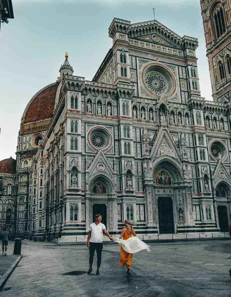 Couple running in front of Florence Cathedral, one of the top things to do in Florence.
