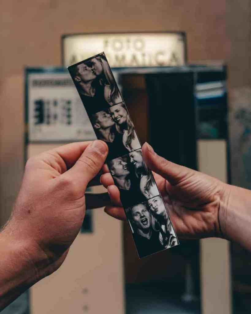 Hands holding out black and white film strip of couple in front of a vintage photo booth.