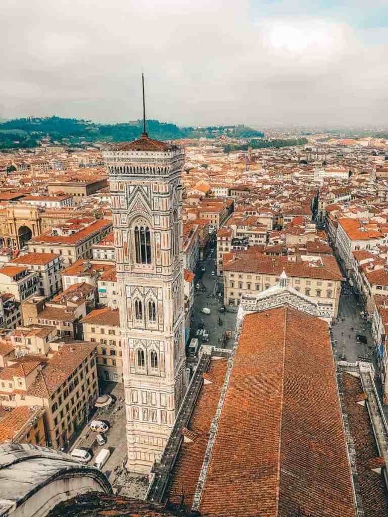 View from the Duomo of Giotto's Bell Tower amidst the brick-topped city of Florence.