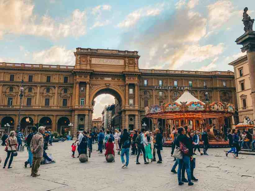 Beautiful Piazza della Repubblica in Florence with arched entrance, antique carousel and many people walking around.