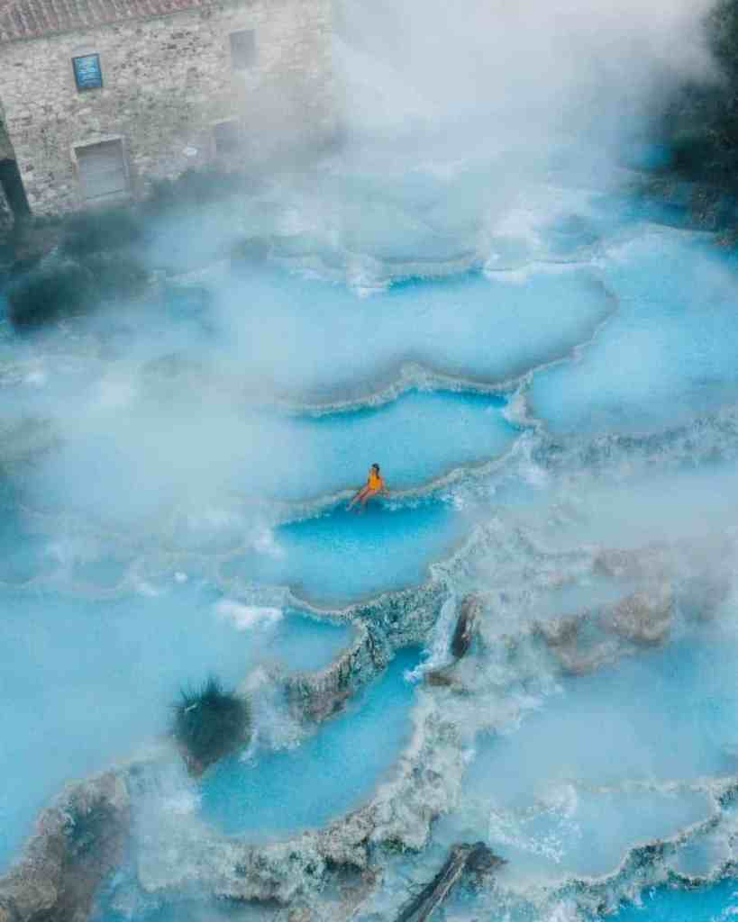 Girl sitting in gorgeous layers of baby blue hot springs in Saturnia Italy