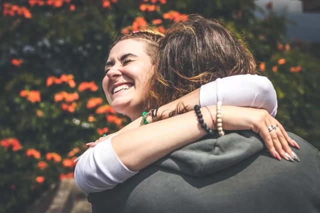 smiling woman hugging another person 2292932