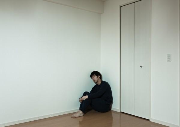 部屋の隅っこで独り寂しく寝落ちする男性