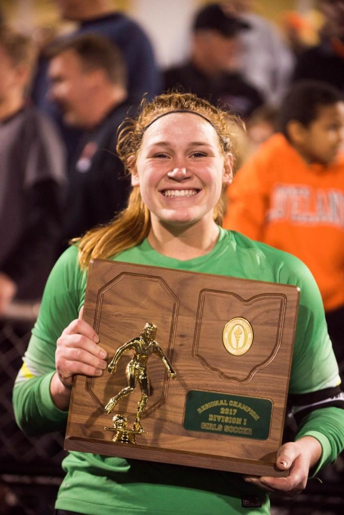 Lauren Parker displays the team's regional champion plaque