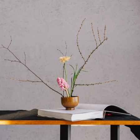Image of a small vase on a book holding branches and flowers