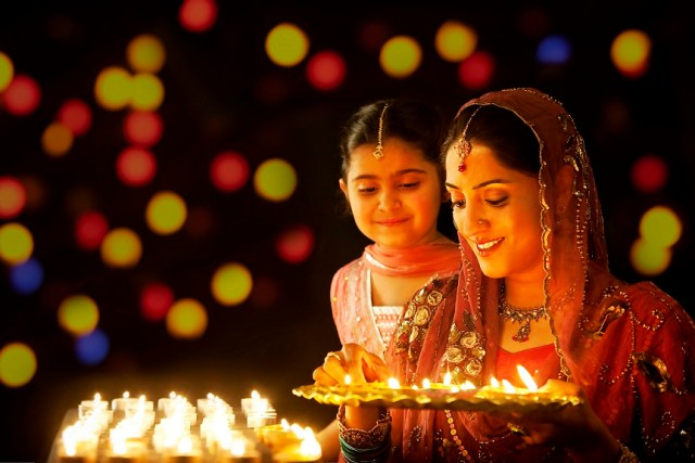 Mother holding a tray of diyas while her daughter looks on